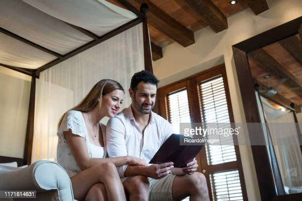 couple reading a guide in a hotel room - beautiful wife pics stock pictures, royalty-free photos & images