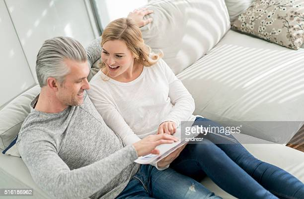 Couple reading a magazine at home