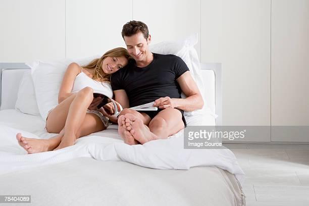 couple reading a magazine - grand lit photos et images de collection
