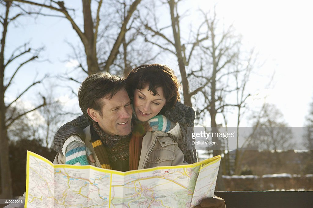 Couple Reading a Map, Woman Standing Behind man : Stock Photo