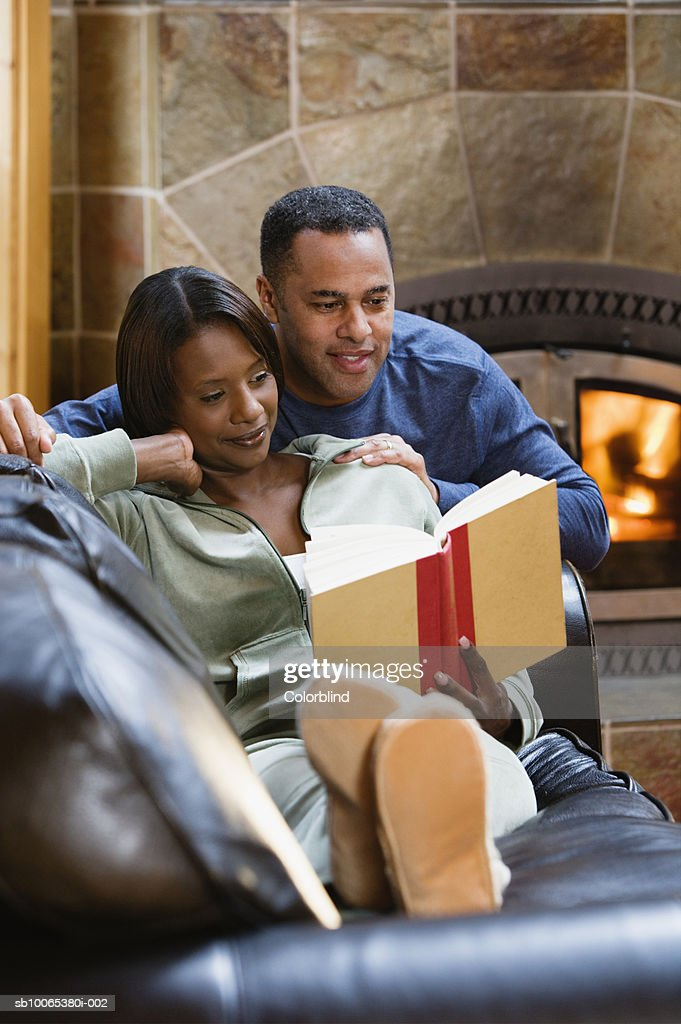 Couple reading book by fireplace : Foto stock