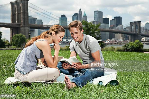 Couple reading book on grass in front of Brooklyn Bridge, New York City, USA