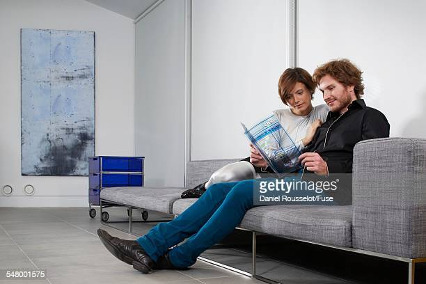 Couple Reading Electronic Paper in Living Room