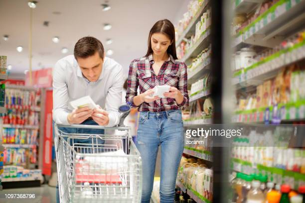 Couple reading label on organic food package