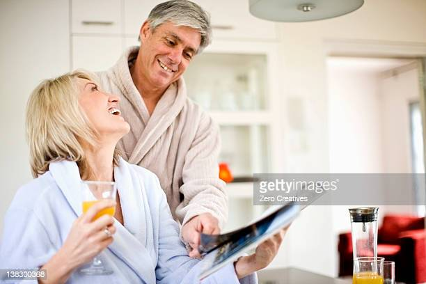 couple reading magazine at breakfast - glass magazine stock photos and pictures