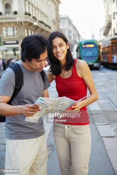 Couple reading map on city street