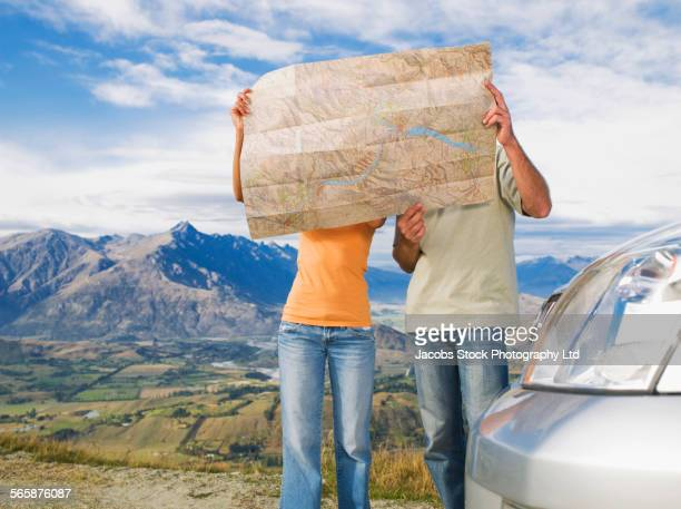 Couple reading map on remote road, Queenstown, South Island, New Zealand