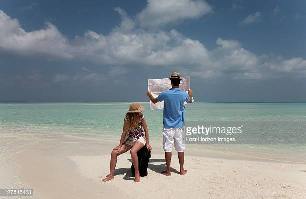 Couple reading map on tropical beach