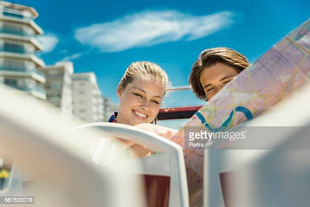 Couple reading map while traveling in tour bus
