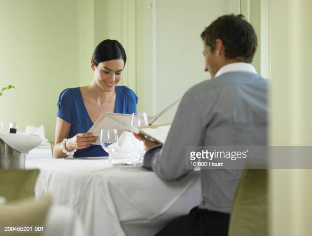 Couple reading menus at table in restaurant