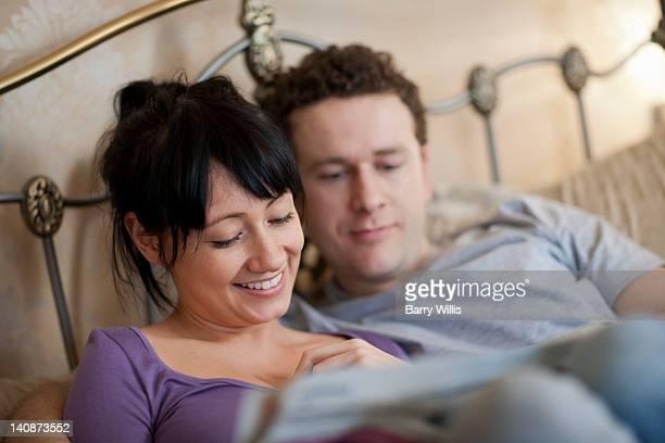 couple reading newspaper in bed - couple au lit photos et images de collection