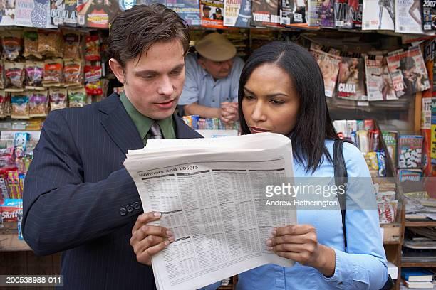 couple reading newspaper in front of kiosk - écriture européenne photos et images de collection