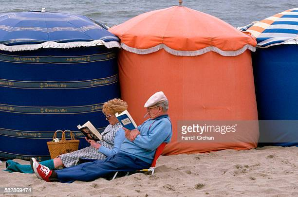 couple reading next to fabric beach tents in trouville, france - calvados stock pictures, royalty-free photos & images