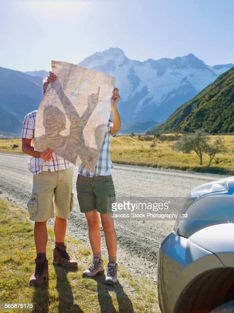 Couple reading roadmap on remote road