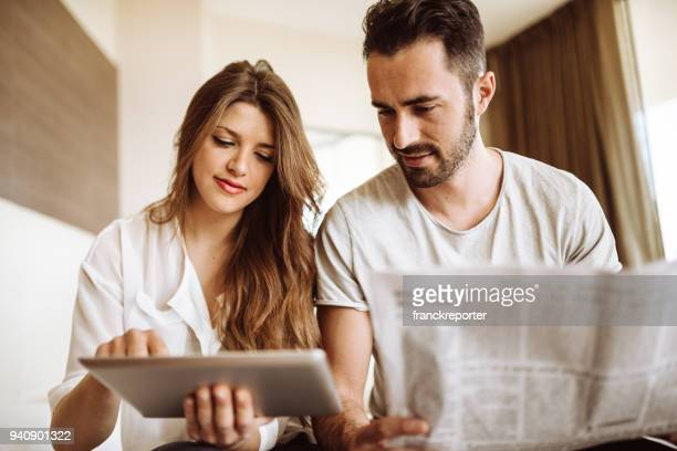 couple reading the newspaper on the hotel - newspaper stock pictures, royalty-free photos & images