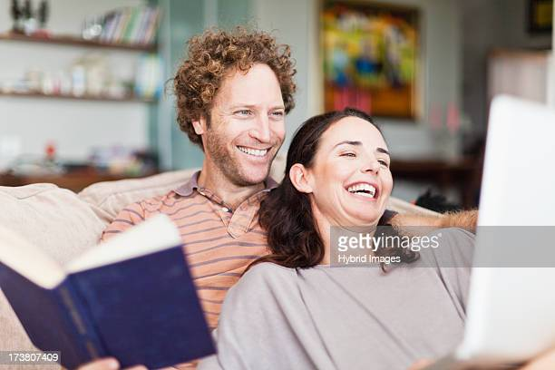 Couple reading together on sofa