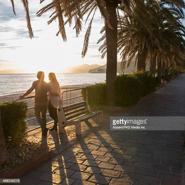 Couple realx by beach rail, near promenade