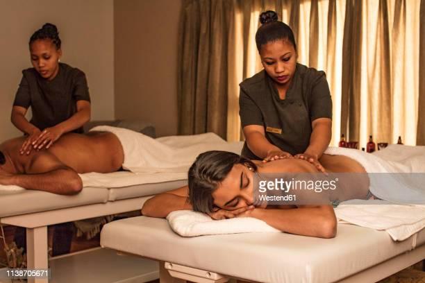 couple receiving a massage in a spa - massage room photos et images de collection