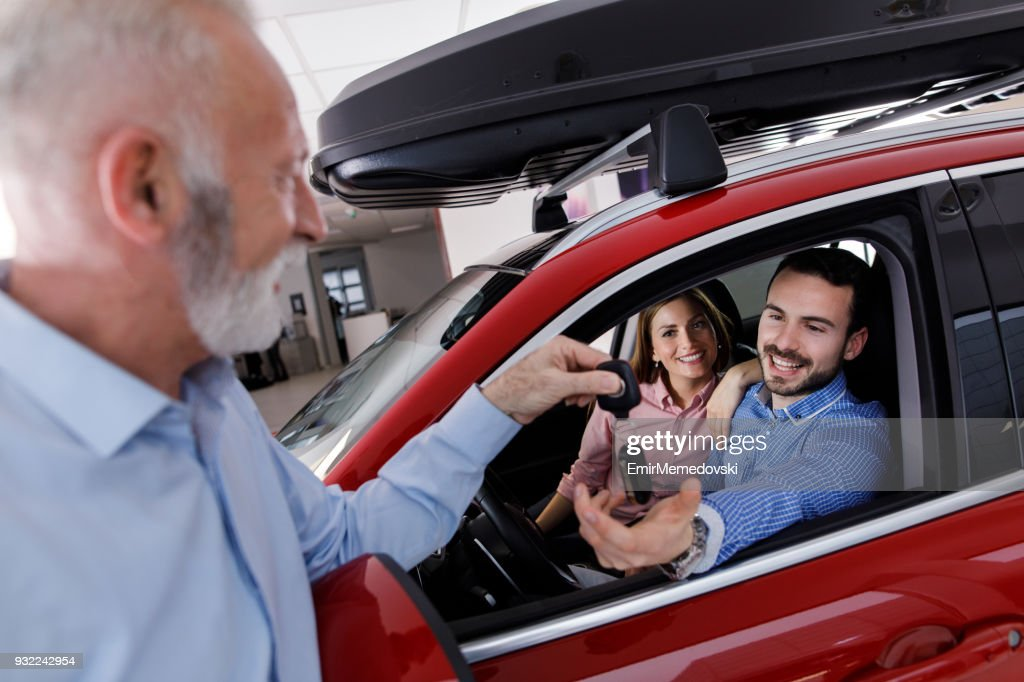 Couple receiving a new car keys from car salesperson : Stock Photo