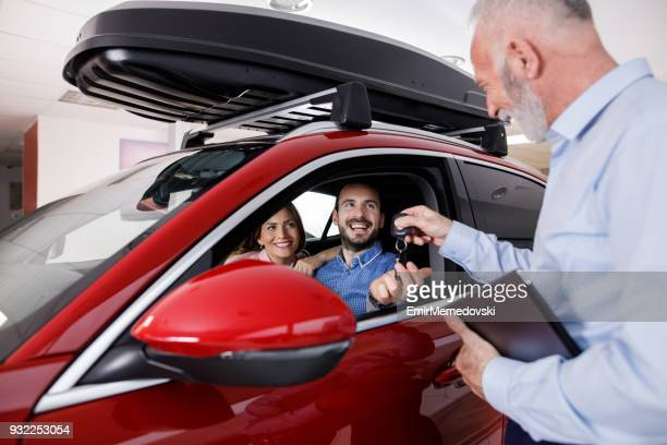 Couple receiving a new car keys from car salesperson