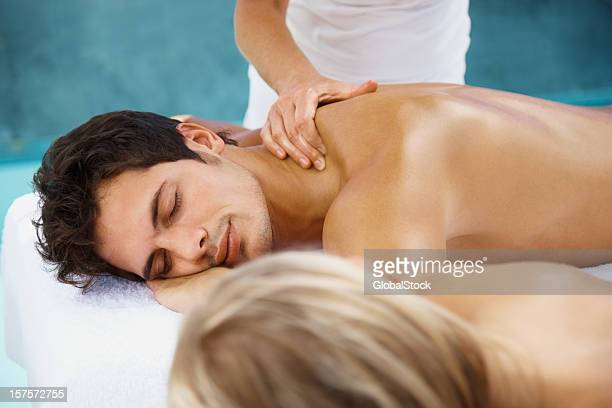 couple receiving body massage and focus on the man - naturist couple stock pictures, royalty-free photos & images