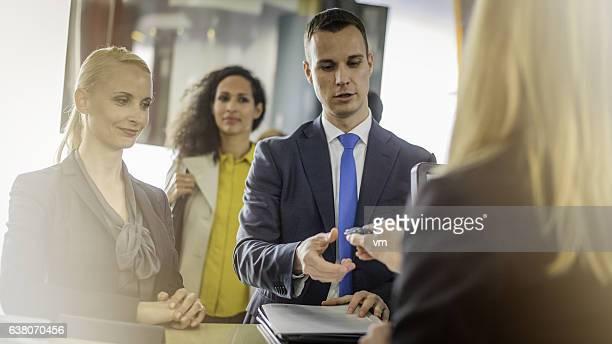 Couple receiving keys from car rental employee