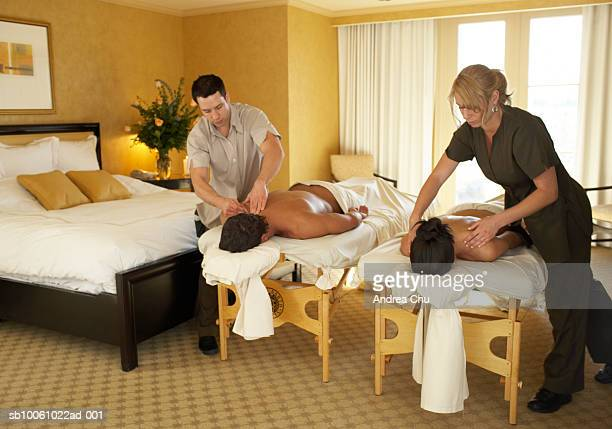 Couple receiving massage by two masseurs