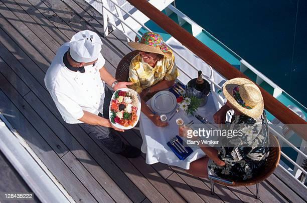 couple receiving meal on deck of passenger liner - kreuzfahrt stock-fotos und bilder
