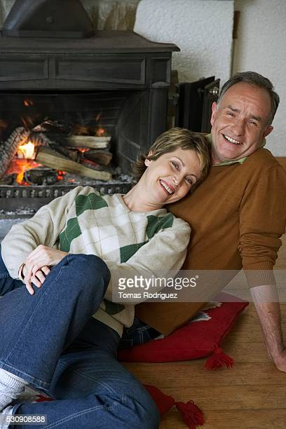 Couple reclining by fireplace