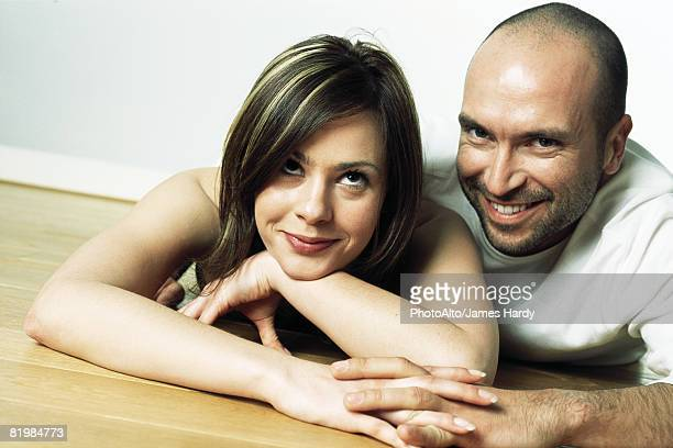 Couple reclining together, smiling, man looking at camera, woman rolling her eyes