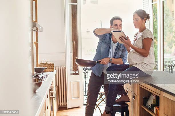 Couple referencing digital tablet while preparing meal