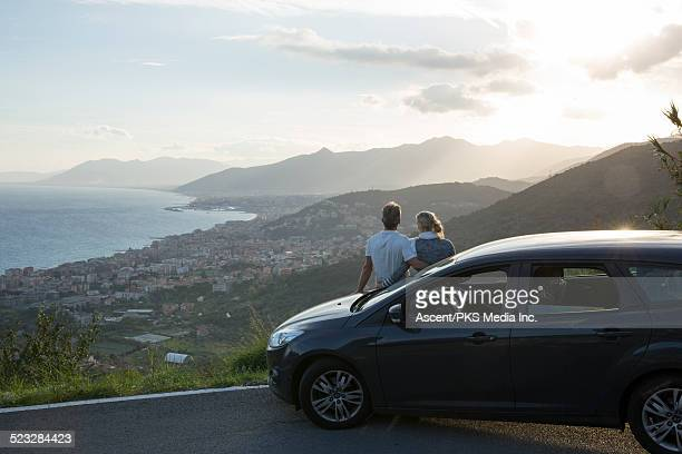 Couple relax against car, look past village to sea