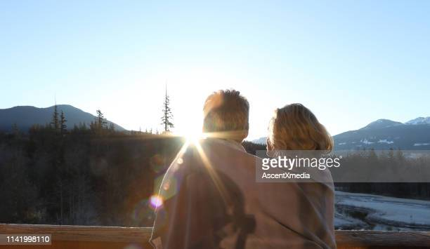 couple relax and embrace each other on patio at sunrise - escapism stock pictures, royalty-free photos & images