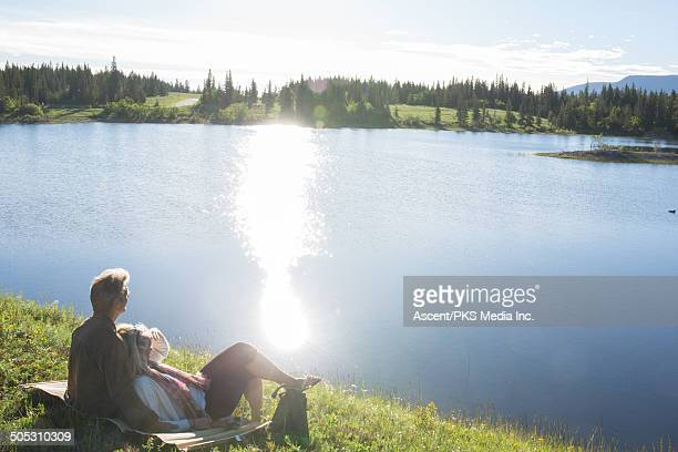 Couple relax at edge of meadow lake, sunrise