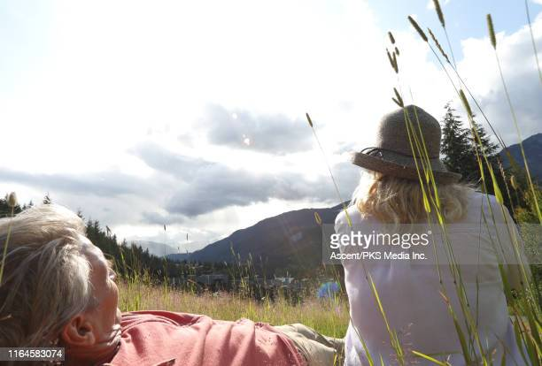couple relax in a mountain meadow in the morning light - early retirement stock pictures, royalty-free photos & images