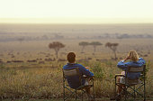 Couple relax in armchairs on the savannah
