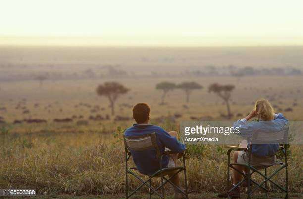 couple relax in armchairs on the savannah - kenya stock pictures, royalty-free photos & images
