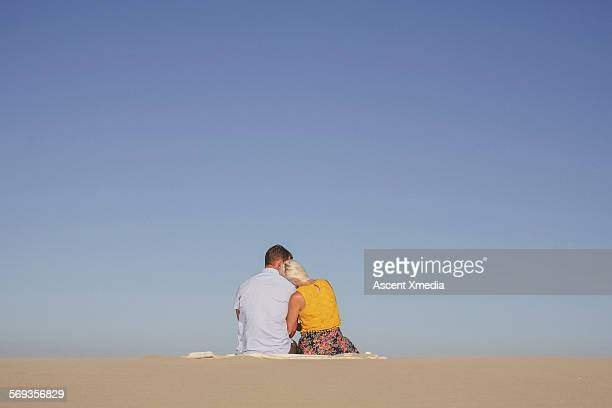 Couple relax in desert landscape, on blanket