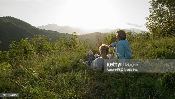 Couple relax in meadow to look out across hills