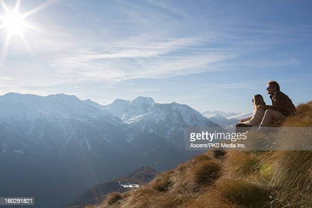 Couple relax in mountain meadow, looking to sun