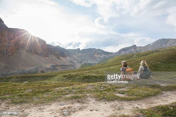 Couple relax in mountain meadow, sunrise