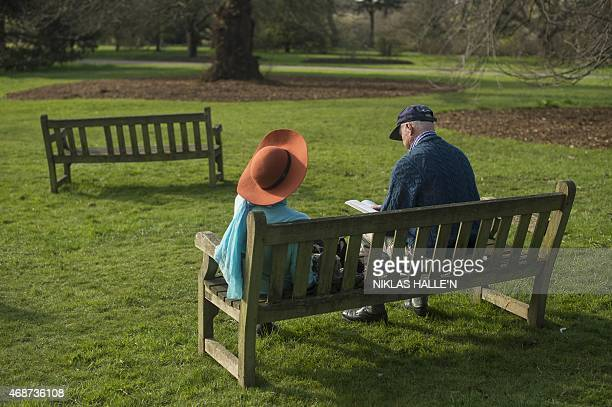 A couple relax in the afternoon sunshine at The Royal Botanical Gardens at Kew in London on April 6 2015 as England basks in higher than expected...