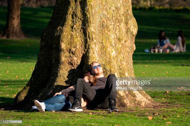 A couple relax in the afternoon sunshine in St James' Park in central London on February 26 as Britain experienced record temperatures for a winter...