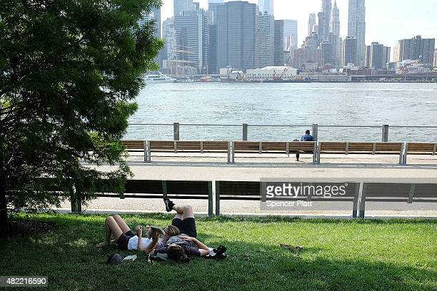 A couple relax in the shade by the East River on a sweltering hot afternoon on July 28 2015 in New York City With temperatures in the 90's and the...