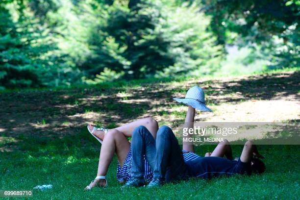 Couple relax in the shade on June 22, 2017 in a garden of Milan during a hot summer-day. - In Italy, forecasters say the current heatwave could turn...