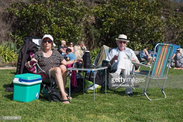 Couple relax in the sun with a picnic on the green opposite the beach in Westcliff on March 30, 2021 in Southend, United Kingdom. Despite todays...