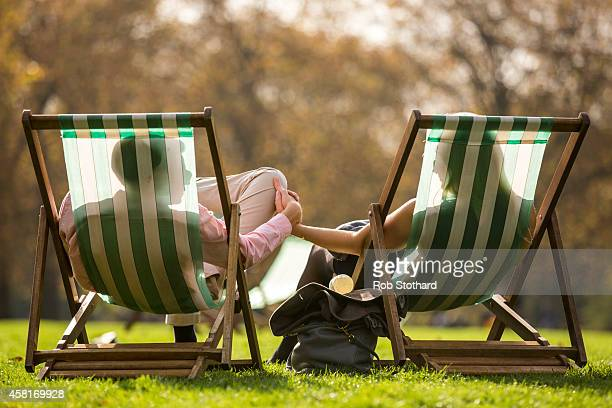 Couple relax in the sunshine in Green Park on October 31, 2014 in London, England. Temperatures in London are forecasted to exceed 20 degrees making...