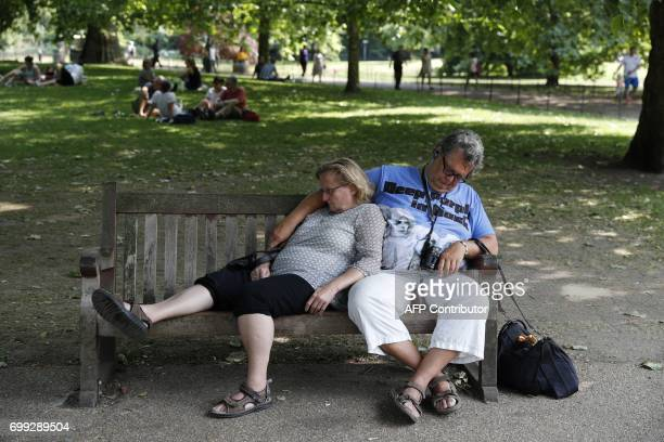 A couple relax on a bench in the hot weather in St James's Park in central London on June 21 2017 Europe sizzled under a continentwide heatwave on...