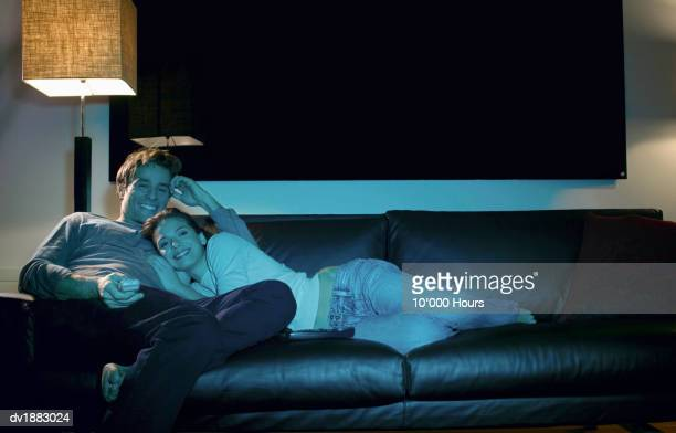 Couple Relax on a Leather Sofa at Night, Watching TV and Smiling