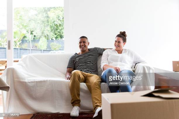 A couple relax on a sofa having moved into a new home